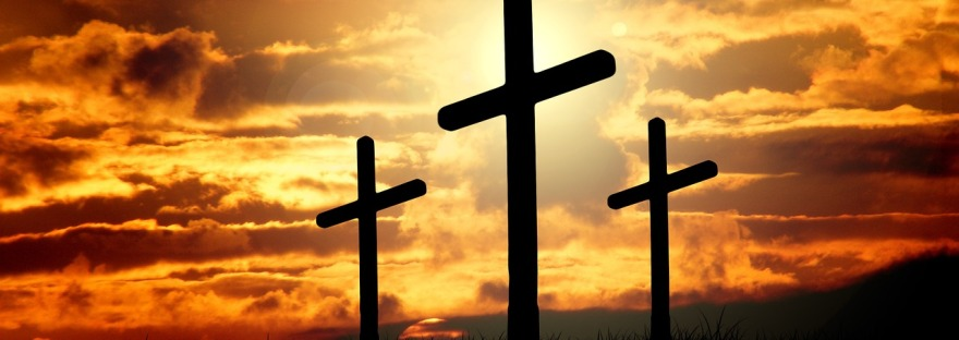 Three crosses in silhouette against a sunset