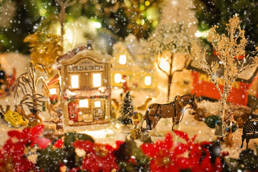 Image shows an idyllic little Christmas village with lights and a horse drawn carriage