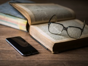 Image shows a smartphone next to a large book