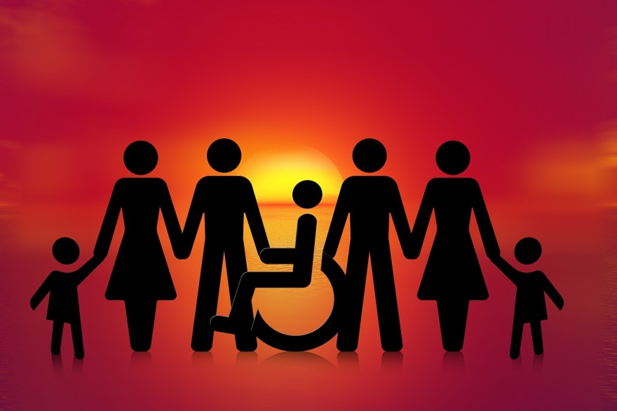 A sunshet shows a family in silhouette. One person sits in a wheelchair