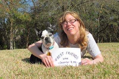 "Amanda Gene lies on the ground with her arm wrapped around Noodles. Noodles is a small black and white Boston Terrier. She holds a sign that says ""Best Friends."""