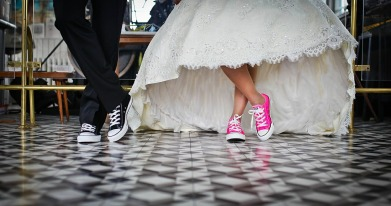 An image of the feet of two people wearing wedding clothes. One each wears a pair of comfortable sneakers.