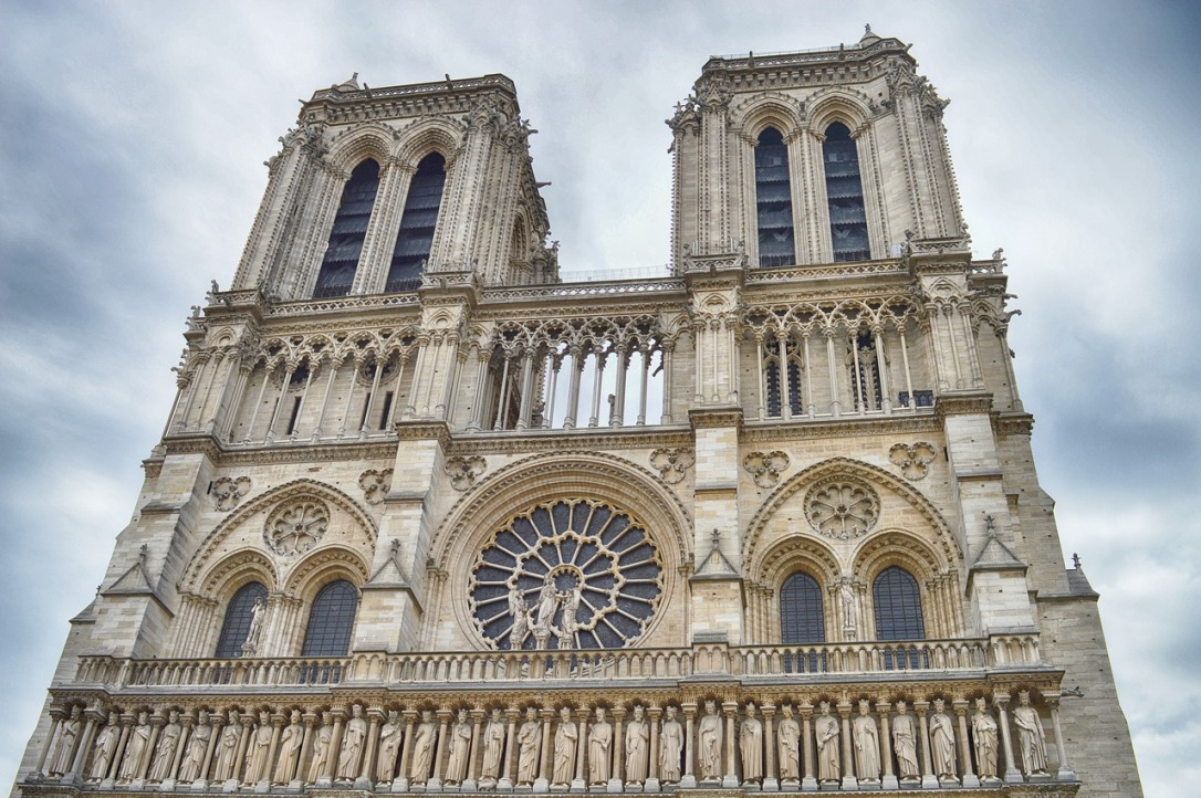 IMage shows the outside of Notre Dame Cathedral. It is a large gothic structure with many statues and flying buttresses.
