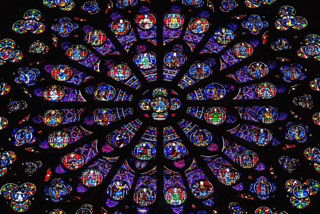 An image shows the stained glass of the rose window in Notre Dame. The window is circular with many bright colors. The window panes look like flower petals