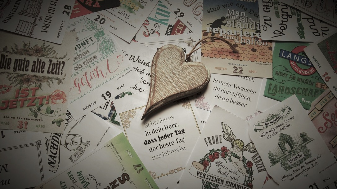 An ornament on the shape of a heart lies on top of a pile of postcards