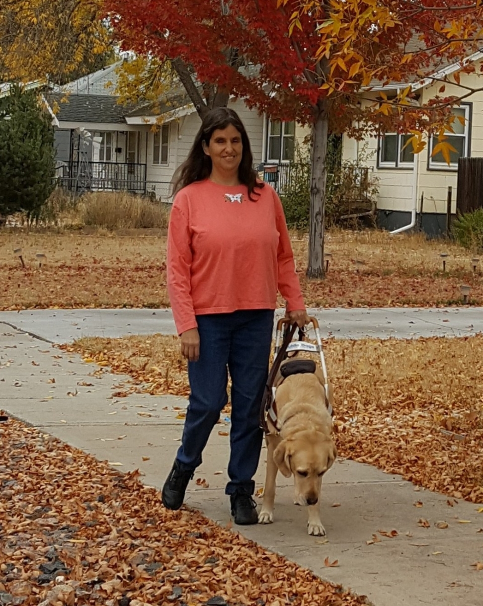 Image shows J.E. Pinto walking on an autumn street with her guide dog. She is a smiling and has long dark hair.