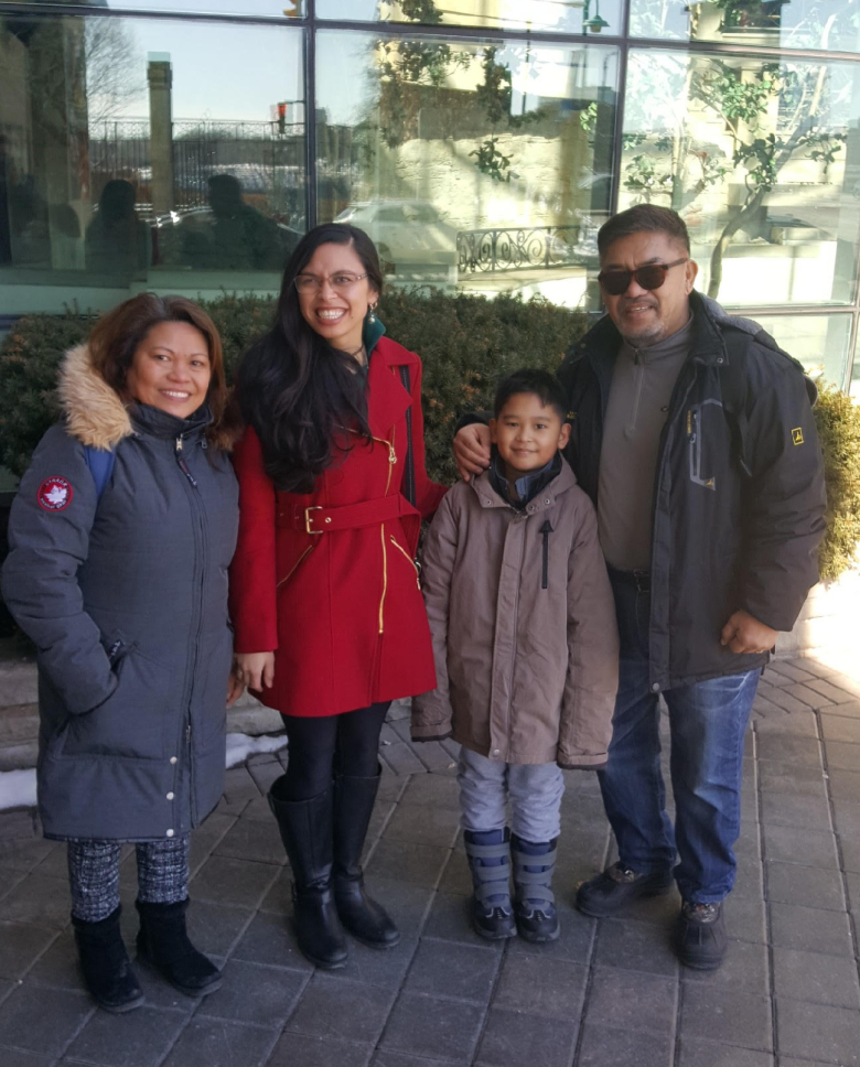 Rebecca wears a red coat and poses outside a restaurant at Niagara Falls her father, aunt, and little brother. Rebecca is half-Filipino and half white.