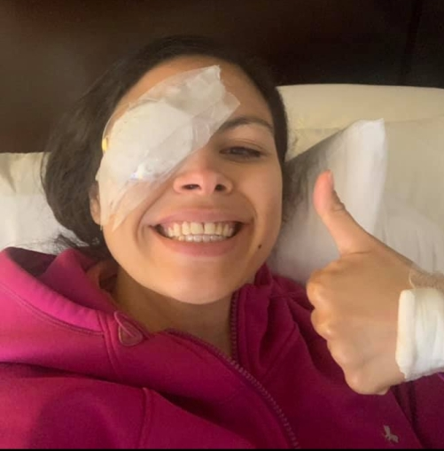 Beckie smiles broadly. Her right eye is covered in gauze