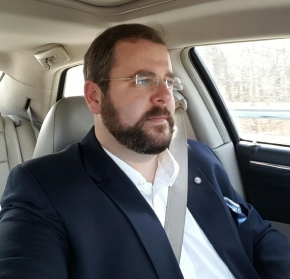 Jeff wears a suit and sits in the driver's seat of a Chrysler