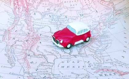 A small red toy car sits on a road trip