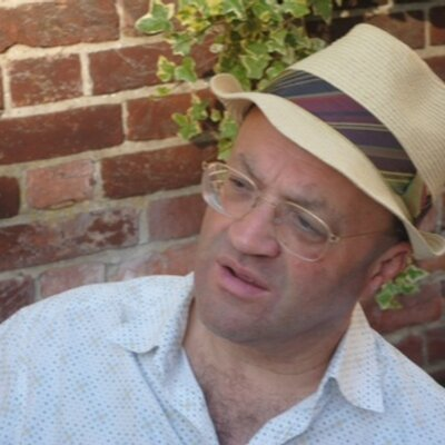 The author wears a hat and glasses
