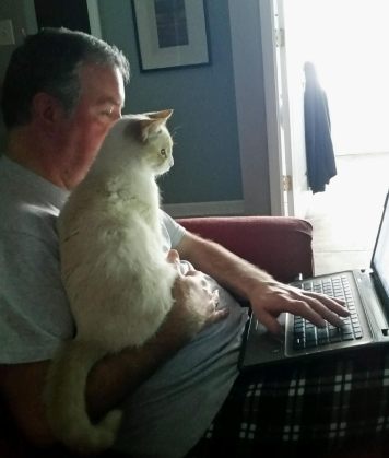 In the photo of the author, his cat sits on his lap while he writes on his laptop