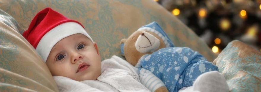 A baby wears a santa hat