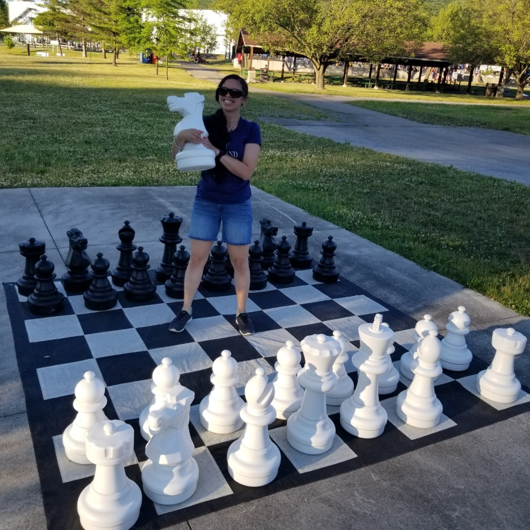 Beckie stands on a giant outdoor chess board. She holds an oversized