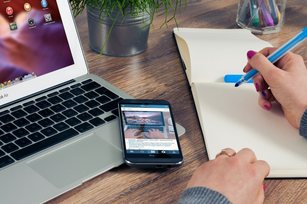 Image shows a person holding a pen and writing while they look at a laptop and an smart phone.