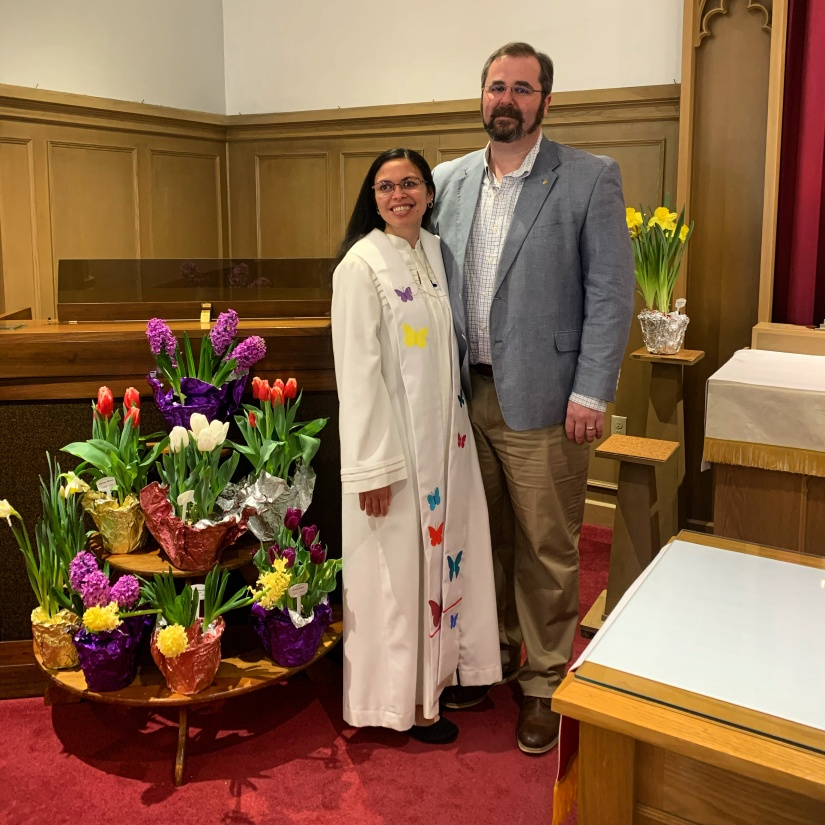 Image shows Rebecca and Jeff standing together and smiling. Rebecca wears a white red and a stole with butterflies.  They are standing in a church near the Easter flowers.