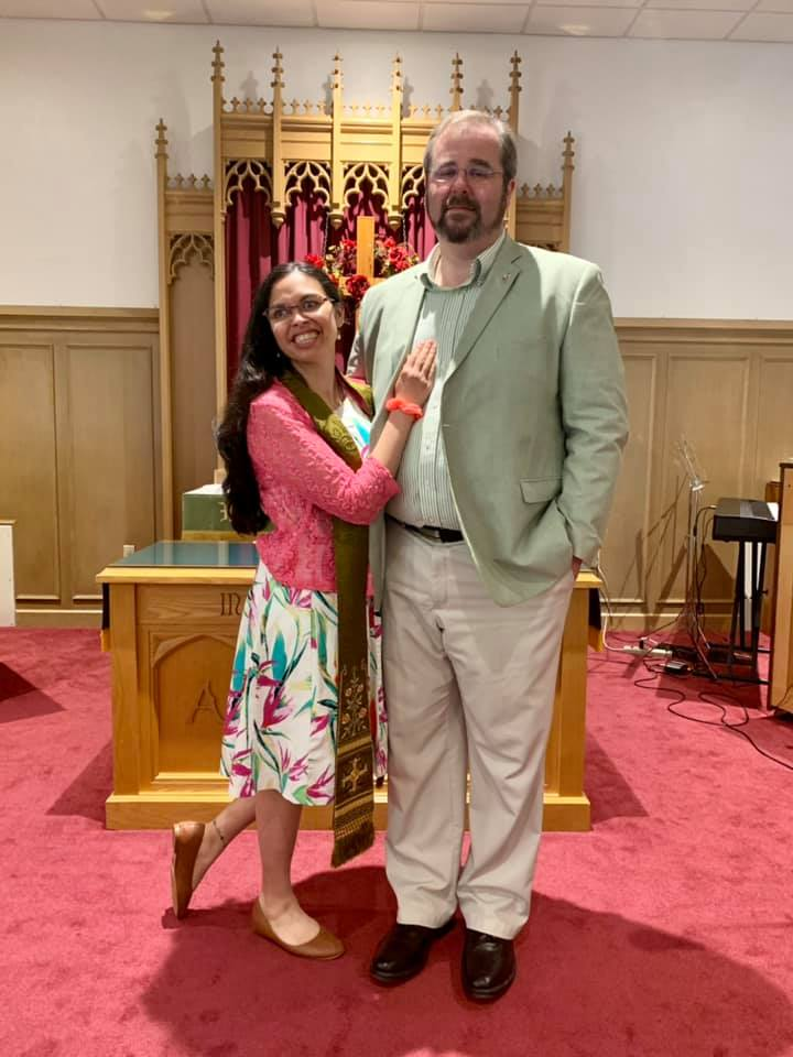 Beckie gives jeff a hug. They are dressed in their sunday best and standing at the front of the church