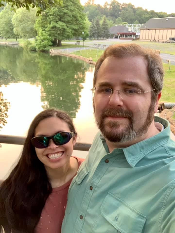 A selfie of jeff and beckie standing on the bridge over the lake at Lakemont park